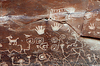 Detail of petroglyphs, pictures etched into the rock surface, depicting ancestral Puebloans along the bottom, with other clans at the top including (left-right) Mountain Lion clan, Horned Toad clan, Parrot clan, Mountain Sheep clan and Eagle clan, on the Petroglyph Point Trail, Mesa Verde National Park, Montezuma County, Colorado, USA. The double spiral is a sipapu, representing the place where Pueblo people believe they emerged from the earth, so the rock face tells the story of various clans, their origins and movements. Mesa Verde is the largest archaeological site in America, with Native Americans inhabiting the area from 7500 BC to 13th century AD. It is listed as a UNESCO World Heritage Site. Picture by Manuel Cohen