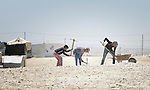Children dig rocks out of the ground in the Zaatari refugee camp near Mafraq, Jordan. They use the material for construction. Established in 2012 as Syrian refugees poured across the border, the camp held more than 80,000 refugees by 2015, and was rapidly evolving into a permanent settlement. The ACT Alliance provides a variety of services to refugees living in the camp.