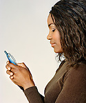 Young African-American woman holding mobile phone.