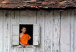 A buddhist novice looking from the window in his dormatory at his temple (Wat) in Luang Prabang, Laos.