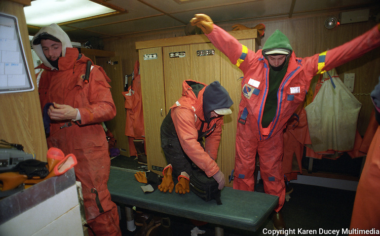 "Crewmen on board the fishing vessel Kiska Sea get ready to go out on deck during the opilio crab season in the Bering Sea.  In this photo they wear a combination of Mustang suits, waterproof gear,  and sweat shirts and pants.  The Bering Sea is known for having the worst storms in the world.  Crab fishing in the Bering Sea is considered to be one of the most dangerous jobs in the world.  This fishery is managed by the Alaska Department of Fish and Game and is a sustainable fishery.  The Discovery Channel produced a TV series called ""The Deadliest Catch"" which popularized this fishery."