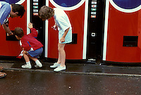 Family looks for soft drinks in vending machines.