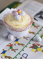 Detail of an Easter cup cake decorated with hard-shelled chocolate eggs and a little bird