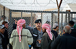 A Jordanian police officer works to establish order during a public distribution of bread in the Zaatari Refugee Camp, located near Mafraq, Jordan. Opened in July, 2012, the camp holds upwards of 50,000 refugees from the civil war inside Syria, but its numbers are growing, and tensions inside the camp regularly boil over into incidents where the police have had to intervene. International Orthodox Christian Charities and other members of the ACT Alliance are active in the camp providing essential items and services.