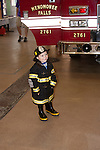 A little girl posing in a firefighter uniform in front of the Menomonee Falls Fire Engine WI