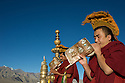 Monks blow conch shells to call monks to morning puja (prayers) at Thiksey Monastery in Ladakh, India.