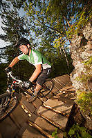 A mountain biker rides the signature rock wall and wooden bridge near the end of The Flow trail of Copper Harbor Michigan.