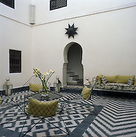 The central courtyard of the riad has wire mesh chairs found in the souk and a geometrically patterned black and white tiled floor