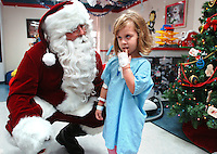 12/12/08--TAMPA--Mila Oliva, 4, talks to Santa Claus a.k.a. Jeff Kritz, a Tampa police officer, as he made his way from room to room in the Children's Medical Center at Tampa General Hospital Friday. Oliva asked for a pink bike for Christams. Santa arrived to the hospital via Aeromed, one of the hospital's medivac units. Photo by Julie Busch
