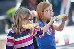 Two girls enjoy corn-on-the-cob at the first Los Altos Farmers Market of the season May 2.