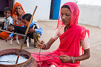 Suki (not her real name), churns milk as her young son plays with a goat in her house in Jhaju village, Bikaner, Rajasthan, India on 4th October 2012. Now 20, Suki was married off at age 12, but only went to live with her husband when she was 14. The three sisters, aged 10, 12, and 15 were married off on the same day by their maternal grandfather while their father was hospitalized. Her husband died three years after she moved in, leaving her with a daughter, now 6, and a son, now 4. She has no parents-in-laws and thus returned to her parents house after being widowed because her brother-in-law, who had become the head of the family after his brother's death, had refused to allow Suki to inherit her deceased husband's fair share of agriculture land. Although Suki's father wants her to remarry, she refuses to, hoping instead to be able to support her family through embroidery and tailoring work. The family also makes hand-loom cotton to subsidize their collective household income. Photo by Suzanne Lee for PLAN UK