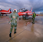 Squadron Leader Duncan Mason of the elite 'Red Arrows', Britain's prestigious Royal Air Force aerobatic team, strides out across a gloomy, rainswept 'apron' at RAF Scampton, Lincolnshire. Squadron Leader Mason will fly up to 6 times daily during winter training ,when weather permits, learning new manoeuvres. Wearing winter green flying suits, their day is spent flying and de-briefing. Mason  wears a green flying suit with anti-g pants and helmet on with its pilot number. He is being greeted by a member of the team's support ground crew who outnumber the pilots 8:1.  The engineer wears a fluorescent yellow tabard and stands politely by the waiting aircraft on the 'line'. He haas already prepared it for flight and helps with any technical issues that may arise. .
