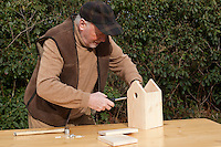 Nistkastenbau, Großvater, Opa  baut einen Vogel-Nistkasten für Meisen aus Holz, fertiger Bausatz