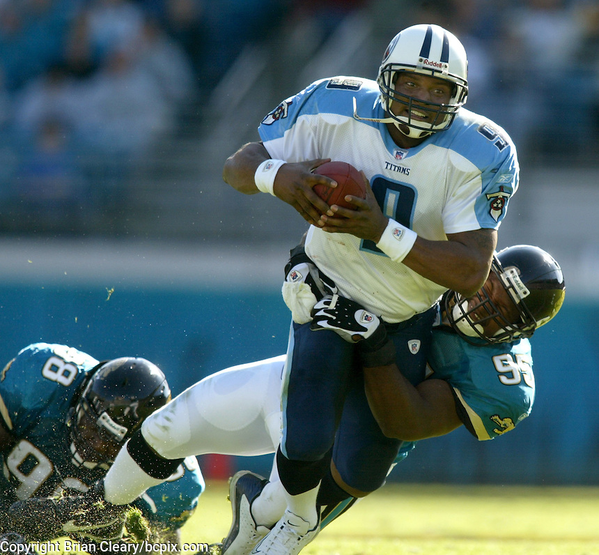 Tennessee Titans quarterback Steve McNair is tackled by Jacksonville Jaguar defensive end Paul Spicer after scrambling during a game against the Jacksonville Jaguars in Jacksonville, FL on Sunday, December 22, 2002.  Tennessee won the game 28 to 10. (Photo by Brian Cleary/www.bcpix.com)