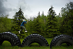 "Simon Reece from Anzac, Alberta, jumps from giant tire to giant tire, a signal of the industrial development in the region. ""We are the land, and the land is us and all of our teachings and values stem from that one."""