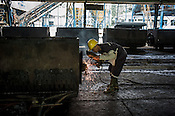 A factory worker mends the trolley at the Sipef oil mill in Sumatra, Indonesia.