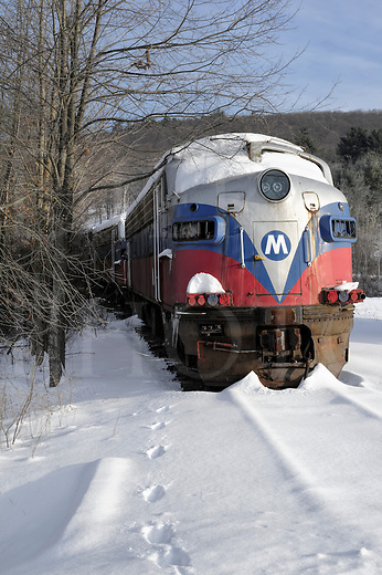 Haunted train sitting abandoned in winter snow and sunlight.
