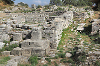 The South Gate of Troia VI, 17th-15th centuries BC, probably the principal entrance to the citadel, in the ruins of the Homeric city of Troy, Hill of Hissarlik, Turkey. Only the roadway survives today, leading in a straight line up into the citadel. It was originally entirely paved with stone slabs and a drainage channel runs beneath the paving stones. Troy was a city, both factual and legendary, in northwest Anatolia and was the setting of the Trojan Wars described in Homer's Iliad. Picture by Manuel Cohen