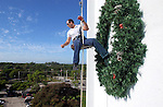 Mike Milner danglesoff the Collier County Government Center after rappelling and checks below with an associate about the placement of the oversized wreath in Naples Florida.