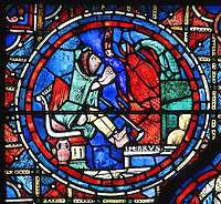 A peasant sits by the fire warming his hands and feet at the flames in the coldest month of the year when the land cannot be worked, section of February from the Zodiac and the labours of the months stained glass window, 1217, in the ambulatory of Chartres Cathedral, Eure-et-Loir, France. This calendar window contains scenes showing the zodiacal symbol with its corresponding monthly activity. Chartres cathedral was built 1194-1250 and is a fine example of Gothic architecture. Most of its windows date from 1205-40 although a few earlier 12th century examples are also intact. It was declared a UNESCO World Heritage Site in 1979. Picture by Manuel Cohen