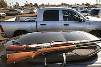 USA. Arizona state. Phoenix. Two rifles on a car's roof in a parking-lot. The firearms' owner want to sell them at the Crossroads of the West Gun Show. A firearm is a portable gun, being a barreled weapon that launches one or more projectiles often driven by the action of an explosive force. Most modern firearms have rifled barrels to impart spin to the projectile for improved flight stability. The word firearms usually is used in a sense restricted to small arms (weapons that can be carried by a single person). The right to keep and bear arms is a fundamental right protected in the United States by the Second Amendment of the Bill of Rights in the Constitution of the United States of America and in the state constitutions of Arizona and 43 other states. 24.01.16 © 2016 Didier Ruef