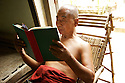 A monk reads in his room. Studying and preserving Buddhist texts is one of the important duties of buddhist monks.