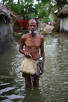 An elderly man wades through the floodwaters. Thousands of people were displaced in Shyamnagar Upazila, Satkhira district after Cyclone Aila struck Bangladesh on 25/05/2009, triggering tidal surges and floods..