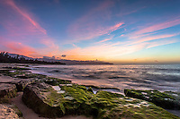 A colorful sunset with algae-covered rocks on the shore of Papa'iloa Beach, North Shore, O'ahu.