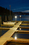 Idaho, North, Coeur d'Alene. A solitary sailboat reflects in the calm water at night under the lights at the Third St. docks on Lake Coeur d'Alene.