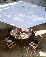 Breakfast on a wooden garden table on the patio under the shade of a white parasol