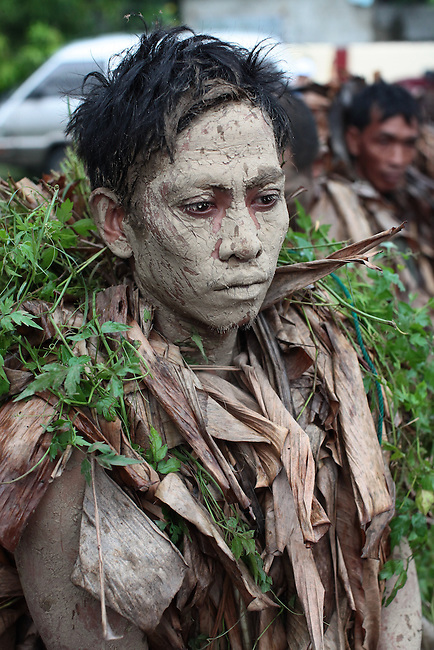 "A young man appears to be in a trance during the annual Taong Putik, or ""mud people,"" festival in Bibiclat, on Luzon island, Philippines. The festival honors St. John the Baptist, and devotees cover themselves in mud, banana leaves and vines, which symbolize the animal skins the saint wore in the Bible. June 24, 2011."