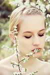 Close portrait of young woman covering her lips with spring flowers while looking down