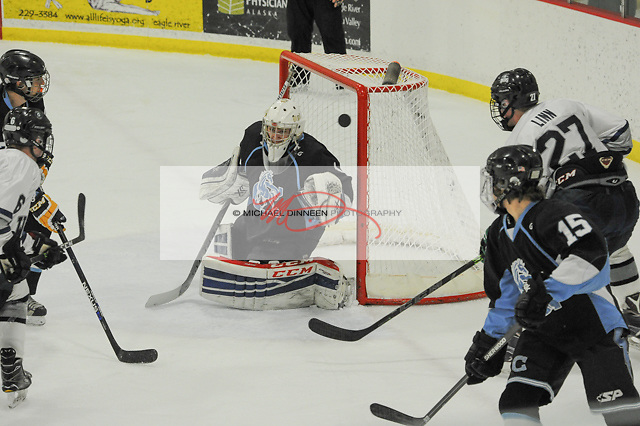 Chugiak goalie Eric Yancey, center, makes a stop as Eagle River's Brandon Lajoie and Joshua Linn close in during the Mustangs' 7-1 win at the McDonald Center, Friday, Dec. 16, 2016.  Photo by Michael Dinneen for the Star.