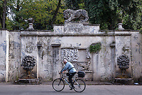 Man rides his bike past a rustic water fountain in the Villa Borghese, Rome, Italy