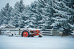 A vintage tractor covered in snow on a farm in Hayden, Idaho.