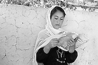 An ethnic Hazara girl studies in an improvised classroom in Malastan, Afghanistan on June 21, 2002. Girls are now allowed an education for the first time since before the rule of the Taliban, but the only books available are islamic religious texts.