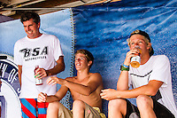 HONOLULU - (Monday, December 3, 2012) Surfboard Shaper Jon Pyzel (HAW), Nathan Florence (HAW) with brother John John Florence (HAW). -- North Shore's John John Florence, the defending champion of the VANS World Cup of Surfing and the VANS Triple Crown series title, posted the highest heat score of the event at Sunset Beach today - 17.8 points out of 20. This is the third of four days of competition and Florence heads into tomorrow's World Cup final rounds as the man to beat.    Florence, 20, hit the waves immediately after 11X world champion Kelly Slater returned to the beach with a heat win, thinking he was the top scorer of the event: 17.04 points. As Slater sat in the VANS LIVE interview chair, he watched the tables turn right in front of his eyes...Florence had reason to be motivated in the 10-foot surf (wave face heights), finding himself out with fellow Sunset surfer Billy Kemper, younger brother Nathan Florence, and VANS Triple Crown contender Fred Patacchia. ..Kemper opened with a perfect 10 wave score after a couple of high risk lip gouges, and John John knew he had no time for warming up in the shifty, lumpy conditions. He answered back with a succession of deep, carving rides. He eventually took the win with Kemper second, Patacchia third, and Nathan Florence fourth. Patacchia's loss likely takes him out of contention for the VANS Triple Crown series title after his top-4 finish at Haleiwa..The second jewel of the $1M VANS Triple Crown of Surfing, the VANS World Cup will require four full days of competition between now and December 6...Winner of the first jewel - the REEF Hawaiian Pro - last week was Sebastian Zietz (HAW). Zietz is seeded through to the round of 64 and will surf on Day 3 of the competition..  Photo: joliphotos.com