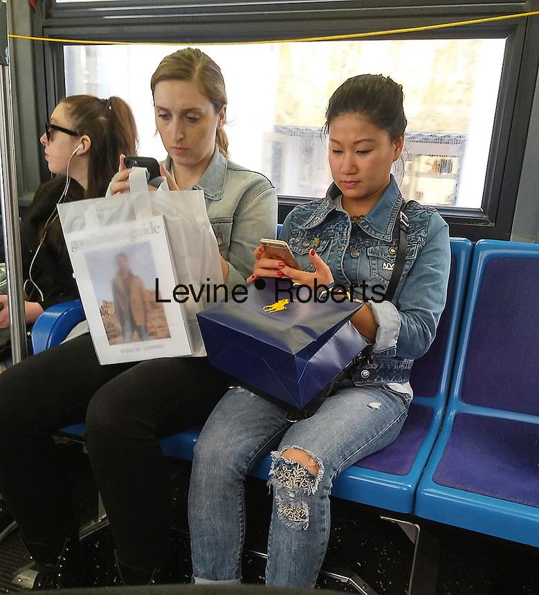 Two women engrossed in their smartphones ride the bus in New York on Friday, March 25, 2016. (© Richard B. Levine)