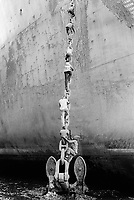 India. Province of Gujarat. Alang. Workers, all men, climb up the anchor's chain to have access to the boat. Ships aground. Vessels stranded. Bottoms of ships at low tide on the shore. Alang, located in the Gulf of Khambhat, is a ships breaking place and is considered as the biggest scrapyard in the world. Ships recycling for its metals. Environmental issues. Hazardous waste. © 1992 Didier Ruef