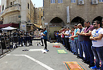 Israeli security forces stand guard as Muslim Palestinians take part in Friday noon prayers in the east Jerusalem neighbourhood of Ras al-Amud on July 31, 2015, following restrictions by Israeli police to allow entry to men only above 50-year-old wanting to access the Al-Aqsa Mosque compound. Photo by Saeb Awad