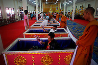 Buddhist monks stand by coffins as people lay in them at Wat Prommanee temple in Nakhon Nayok province May 28, 2011. Hundreds of Buddhist believers pay small fee to lay in nine pink coffins at 9:09 am and 1:09 pm every day in Wat Prommanee temple during its unusual daily resurrection service that they believe will wash away bad luck and prolong life.      REUTERS/Damir Sagolj (THAILAND)