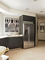 A stylish, modern kitchen with matt grey units and polished marble floor.