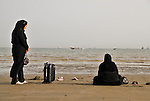 Women with luggage waiting on the beach. Bandar-e-Abbas, Iran