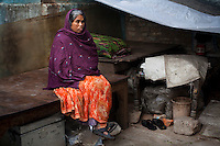 Urmila Maurya, 38, sits on a table, one of her only two pieces of unharmed furniture left of what was once her slum home in the institutional area of Lodi Colony, an upmarket area in New Delhi, India on 03 January 2012. A mother of 2, she spends her days on the pavement stringing flowers into garlands for devotees at the nearby Hindu temple. At night, she lays down on the same plastic tarpaulin she uses for the flowers but claims that the police come and tear it up in an attempt to discourage her from squatting in the open. Photo by Suzanne Lee for The National