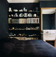 A dramatic black palette is the backdrop to an antique gilt mirror above a marble fireplace in the bedroom. Books and other items are carefully arranged on a shelf in the recess beside the chimney breast
