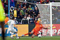 Zlatan Ljubijankic of Slovenia (L) slots the ball past USA goalkeeper Tim Howard to score his sides second goal