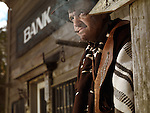 Cowboy with a cigar in his hand standing in front of a bank building