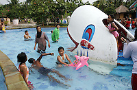 People swim in a water park in northern Jakarta. Many richer communities in the city have been accused of distancing themselves of the problems faced by the residents of poorer communities, who are the first to feel the effects of flooding and the subsequent social and health problems.