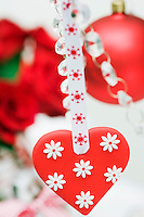 Detail of a red and white heart suspended from a crystal candelabra on a length of ribbon
