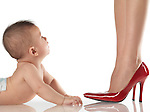 Six month old baby boy looking up at his dressed up mother wearing red high heel shoes